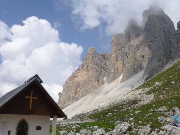 The Tre Cime peaks looming over a historic little church in the Dolomites.