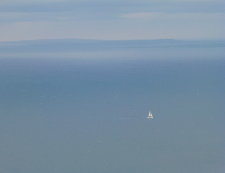 A lone sailboat out on the water surrounding the Cliffs of Moher in Midwest Ireland.