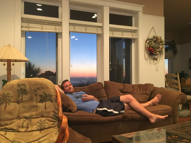Lounging in comfort in our vacation rental -- look at those ocean and sunset views through the window!