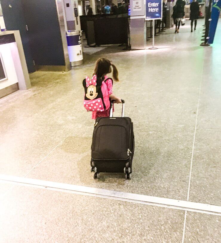 When packing while traveling with kids, get your child their own luggage! She was so proud to wear her backpack and insisted on pulling our carry-on suitcase through the airport.