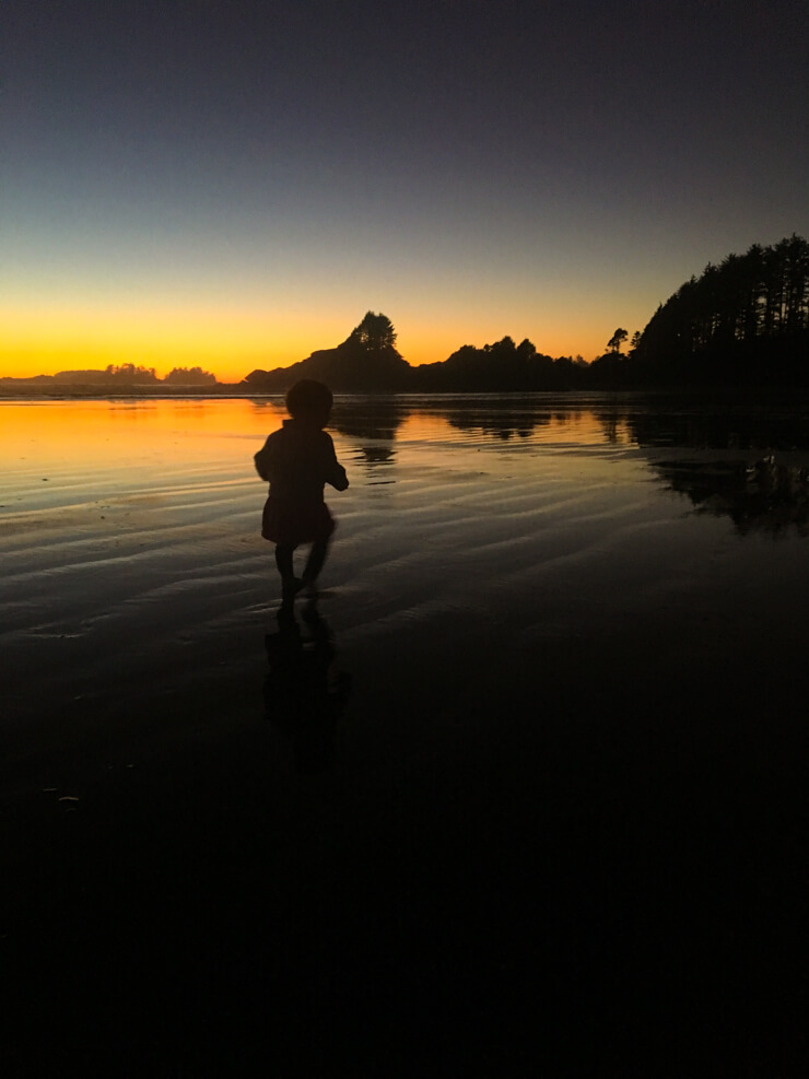 Toddler running around on the beach during a Tofino sunset in British Columbia