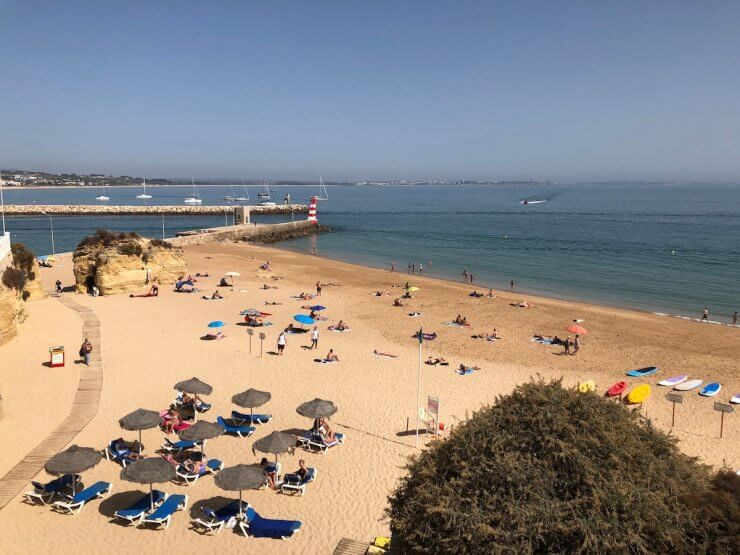 Serene beach in Lagos, Portugal with beach umbrellas and sunbathers