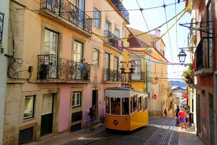 One of Lisbon's Iconic Yellow Trams in the Alfama District with colorful streamers overhead.