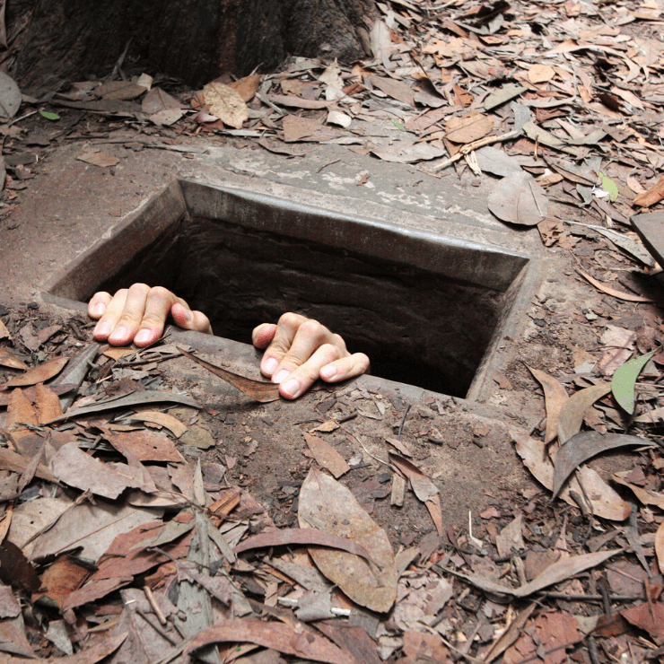 A person coming out of one of the small Cu Chi Tunnels.