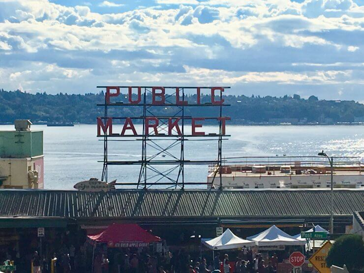 Pike Place Market sign with Elliott Bay behind it. Pike Place Market is a must-see if you have one day in Seattle.