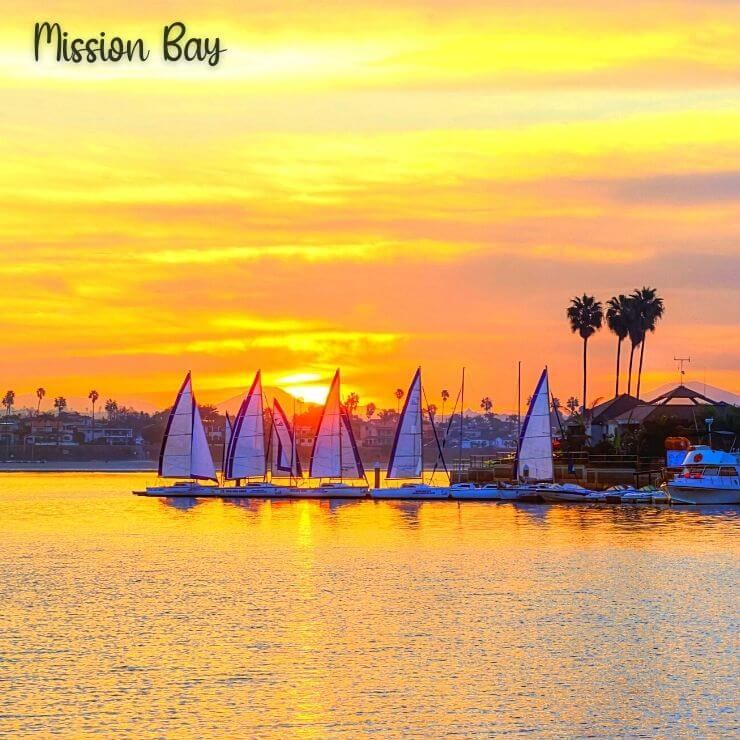 Mission Bay at sunset with sailboats lining the horizon.